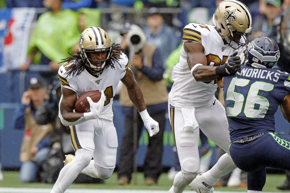 New Orleans Saints running back Alvin Kamara runs against Seattle Seahawks linebacker Mychal Kendricks as tight end Jared Cook blocks during the game on September 22, 2019 at the CenturyLink Field in Seattle, WA.