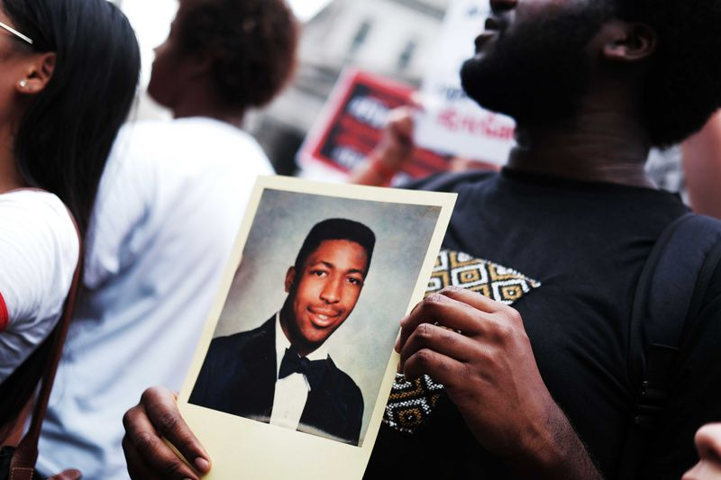 A man holds a photo of Eric Garner during a demonstration.