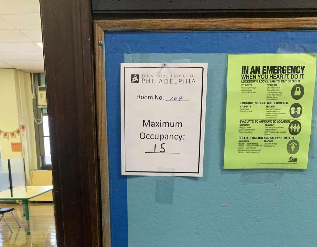 """A sign posted outside a classroom on a bulletin board that reads """"maximum occupancy: 15""""."""