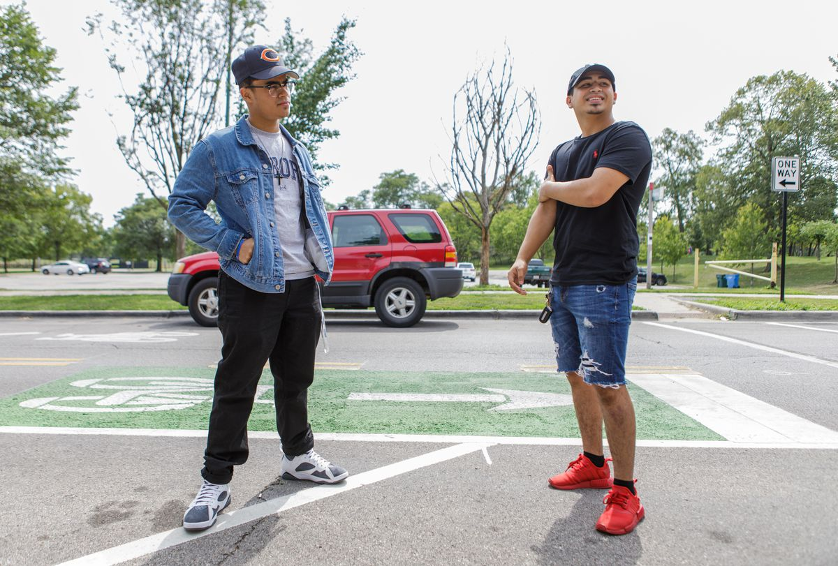 Brian Rivera, left, and Yuan Moreno stand on the bike lane north of Riis Park in the Belmont Cragin neighborhood.