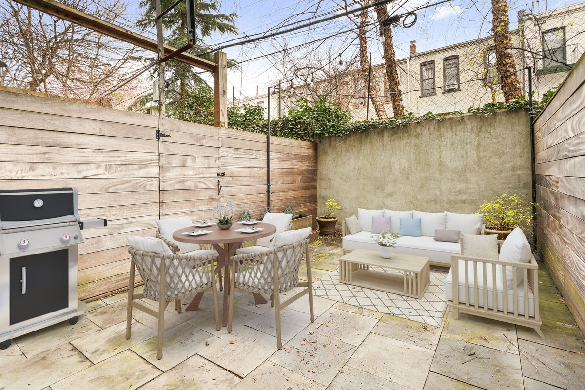 A garden with wooden fences, beige tiles, a small dining table, and two white couches.