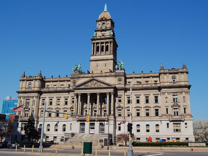 The exterior of the Old Wayne County Building in Detroit. There is a tower in the middle and the entrance has columns over it.