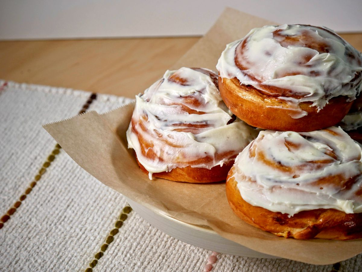 Three iced cinnamon rolls stacked on a plate on a wooden table