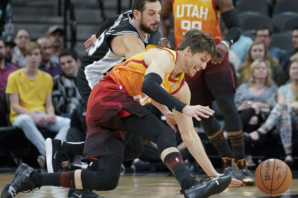 Utah Jazz guard Kyle Korver, front, chases the ball against San Antonio Spurs guard Marco Belinelli during the first half of an NBA basketball game, Sunday, Dec. 9, 2018, in San Antonio. (AP Photo/Darren Abate)