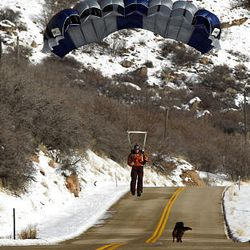 Neil Amonson walks back to his car with his dog after BASE jumping in Echo Canyon.