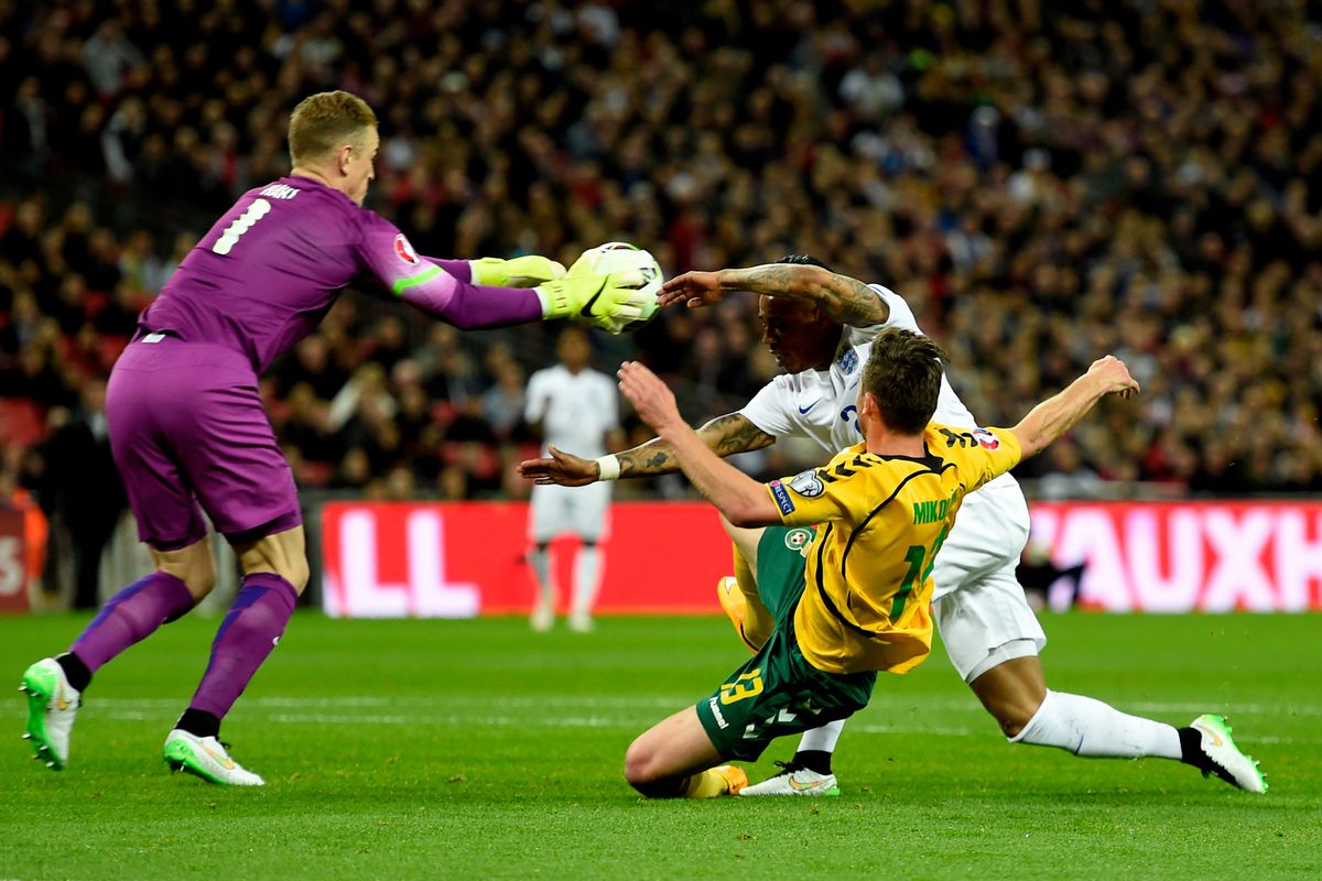 Nathaniel Clyne of England heads the ball back to Joe Hart of England under pressure from Saulius Mikoliunas of Lithuania during the EURO 2016 Qualifier match between England and Lithuania at Wembley Stadium on March 27, 2015 in London, England.
