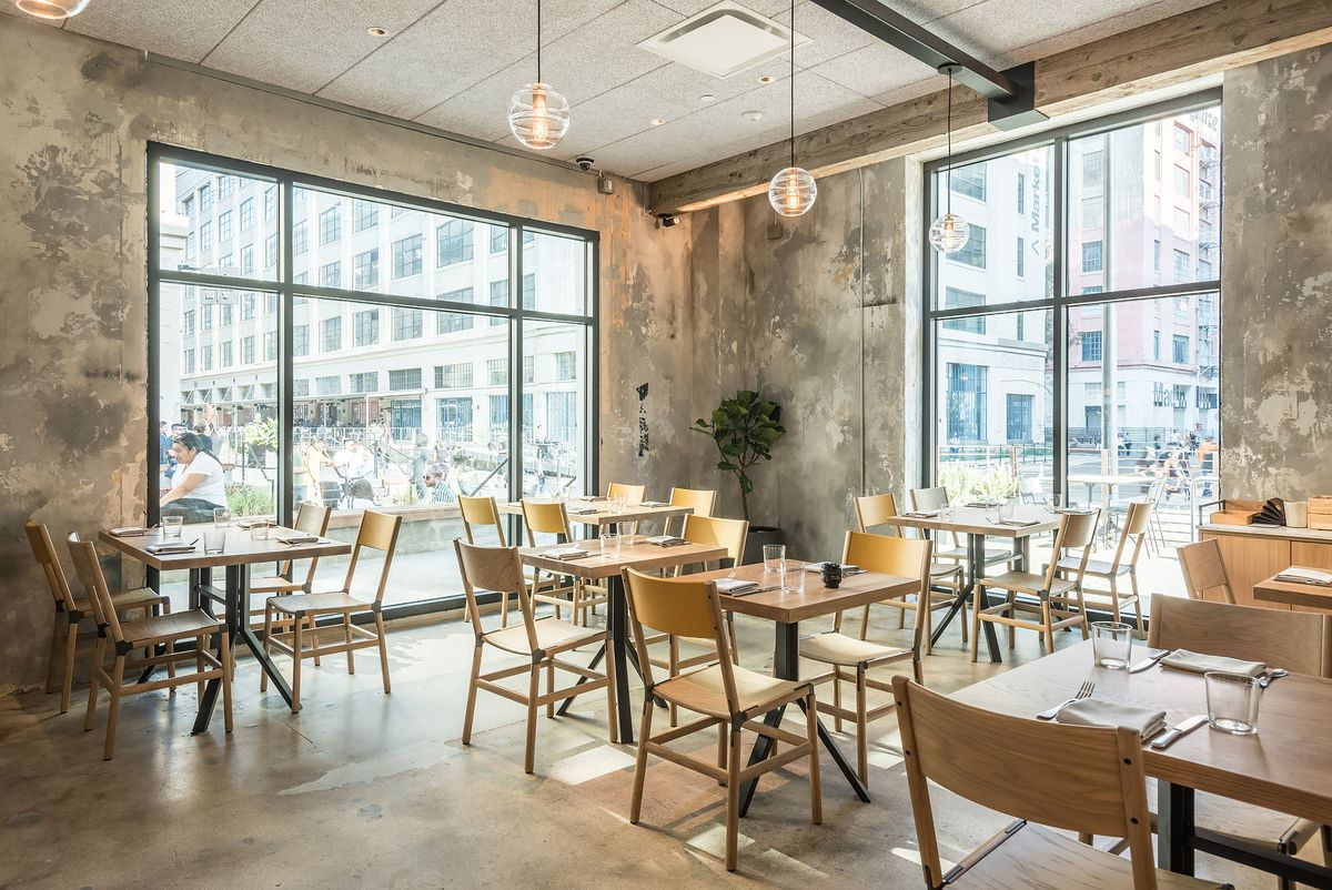 Big warehouse windows and wooden tables at a new restaurant.