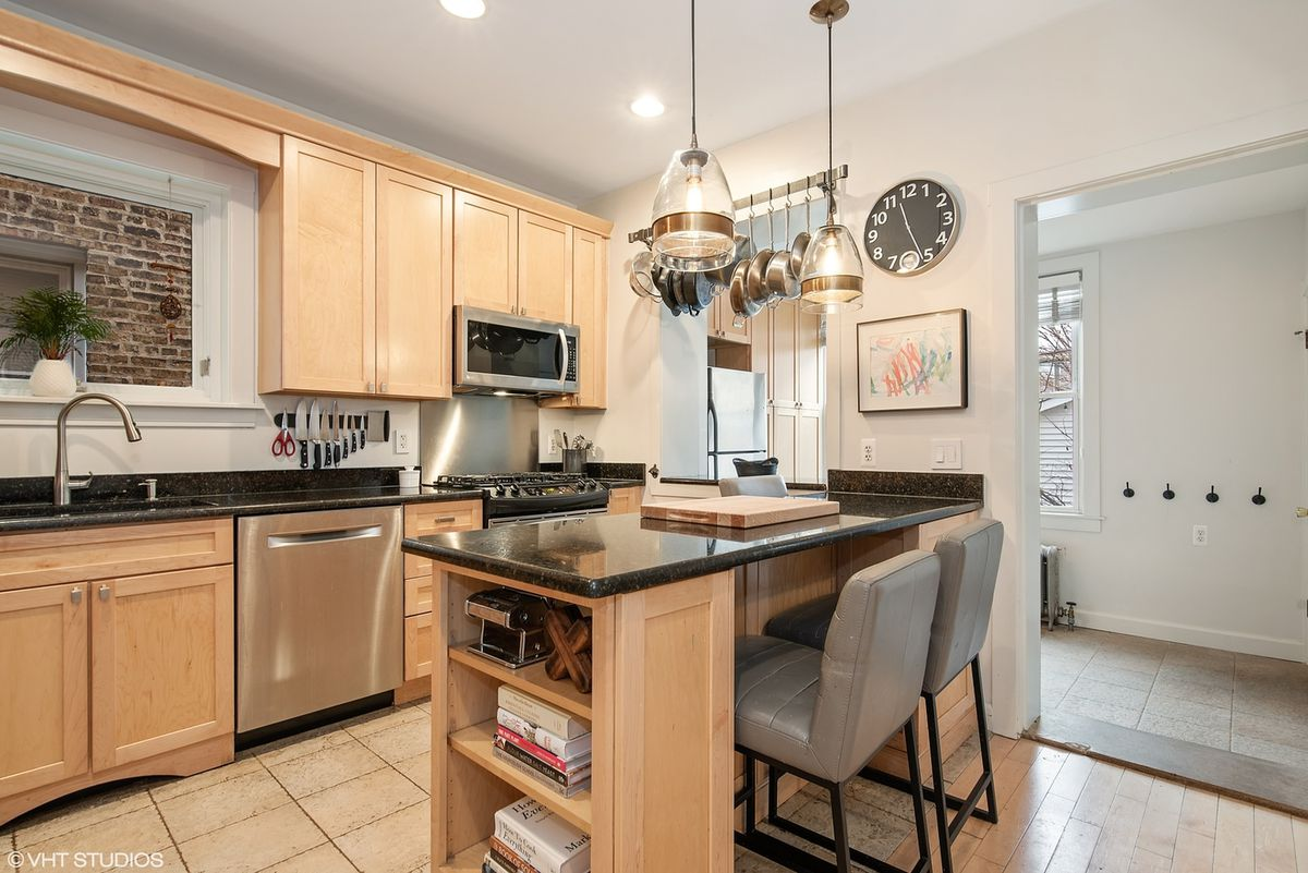 A kitchen with an island, blonde cabinets, stainless steel appliances, and black countertops.
