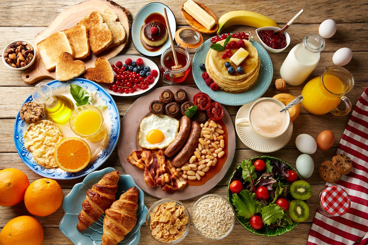 Several plates of breakfast food, including eggs, sausage, pancakes, toast, croissants, and fresh oranges seen from above.
