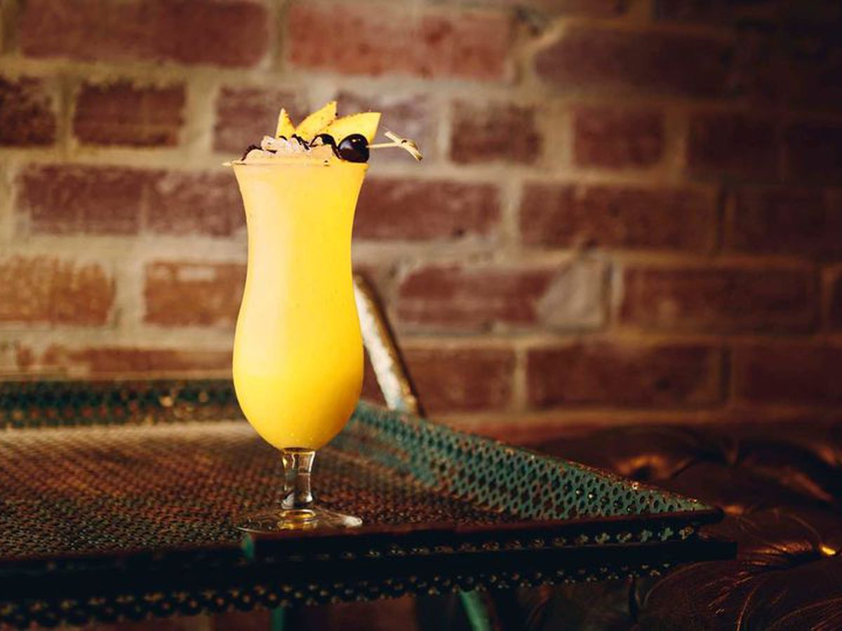 A non-alcoholic drink in a hurricane glass, topped with a garnish of fruit. The yellow drink is on a dimly-lit bar with a brick wall behind it.