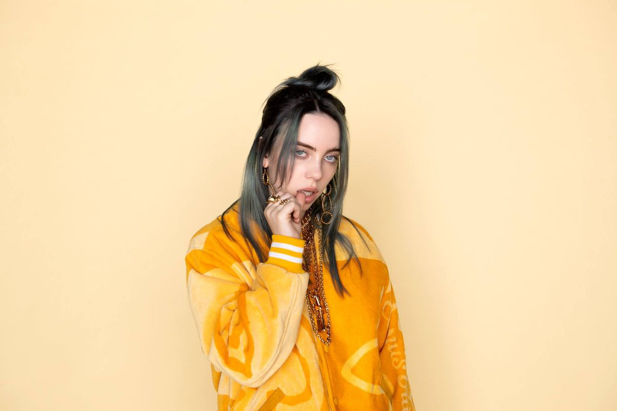Billie Eilish stares at the camera against a yellow background.