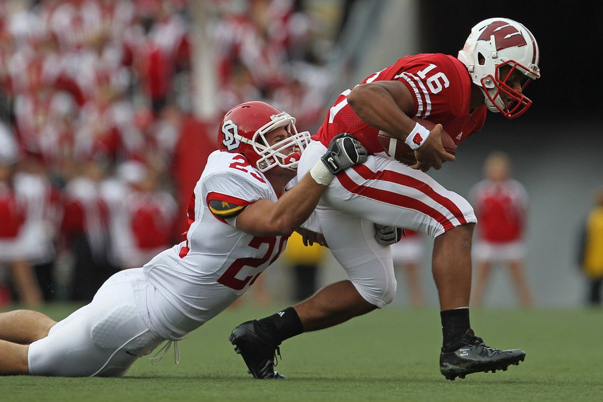 MADISON, WI - SEPTEMBER 24: Russell Wilson #16 of the Wisconsin Badgers tries to break away from Andrew Meier #29 of the South Dakota Coyotes at Camp Randall Stadium on September 24, 2011 in Madison Wisconsin. (Photo by Jonathan Daniel/Getty Images)