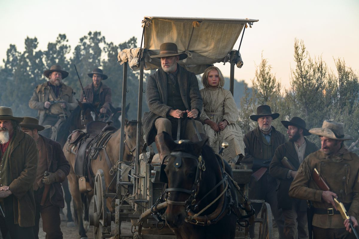 Captain Jefferson Kyle Kidd (Tom Hanks) and Johanna Leonberger (Helena Zengel) ride in a wagon in News of the World