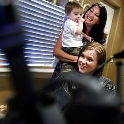 Hair stylist Jessica Bronson holds her son, Blake, while cutting Karah Mackay's hair at her West Valley home on Tuesday, September 27, 2011.  Bronson is a self-employed hair stylist who works out of her home so that she can spend more time with her kids.
