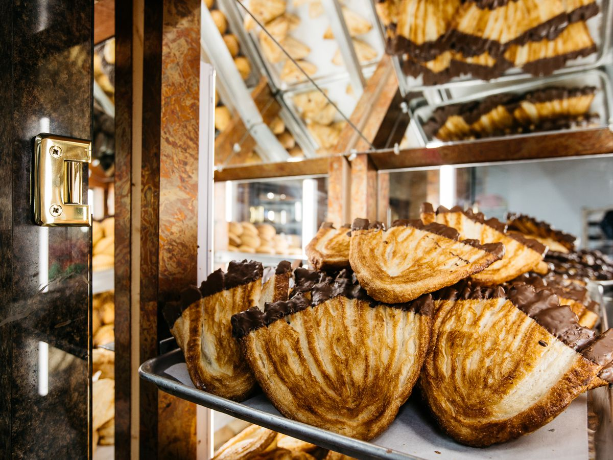 Chocolate dipped pan orejas in a brightly lit pastry case.