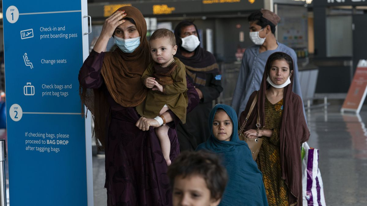 Families evacuated from Kabul, Afghanistan, walk through a terminal upon arrival at Washington Dulles International Airport.