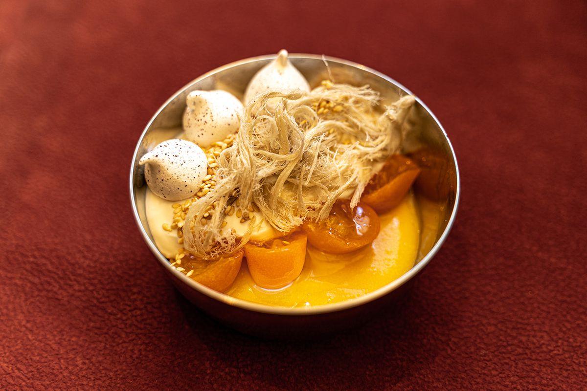 Bowl of Meyer lemon curd with rose meringue and sesame halva
