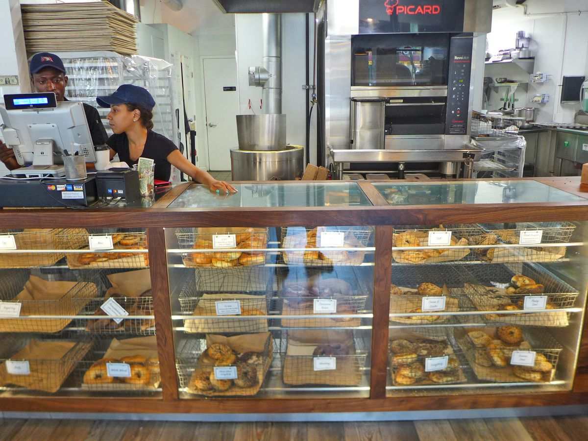 A glass counter with bagels in baskets and two employees by the register to one side.