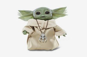 An in-motion product shot of an animatronic Baby Yoda toy