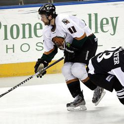 John Armstrong, of Utah, comes away with the puck against Judd Blackwater of Las Vegas as the Utah Grizzlies face the Las Vegas Wranglers in ECHL hockey at the Maverik Center in West Valley City, Monday, April 2, 2012.