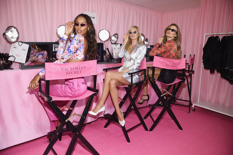 Victoria's Secret models Jasmine Tookes, Elsa Hosk, and Josephine Skriver pose on director-style chairs during a taping of the 2018 fashion show.