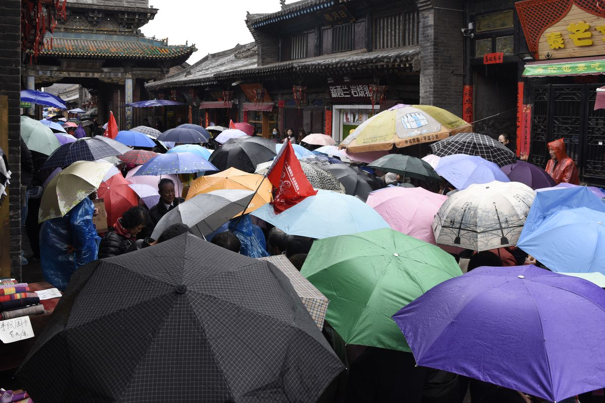 A group of tourists holding umbrellas walks through a narrow ally under a traditional Chinese gate
