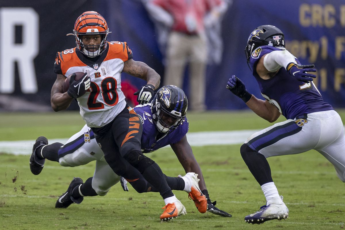 Joe Mixon #28 of the Cincinnati Bengals carries the ball as Jaylon Ferguson #45 and L.J. Fort #58 of the Baltimore Ravens defend during the second half at M&T Bank Stadium on October 11, 2020 in Baltimore, Maryland.