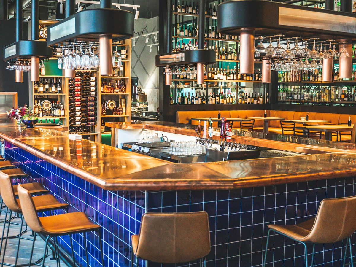 A copper topped bar dominates a cozy room. Underneath it, cobalt blue tiles with white grout make a bright contrast. Contemporary leather bar stools line the bar and open air shelving hangs above it all.