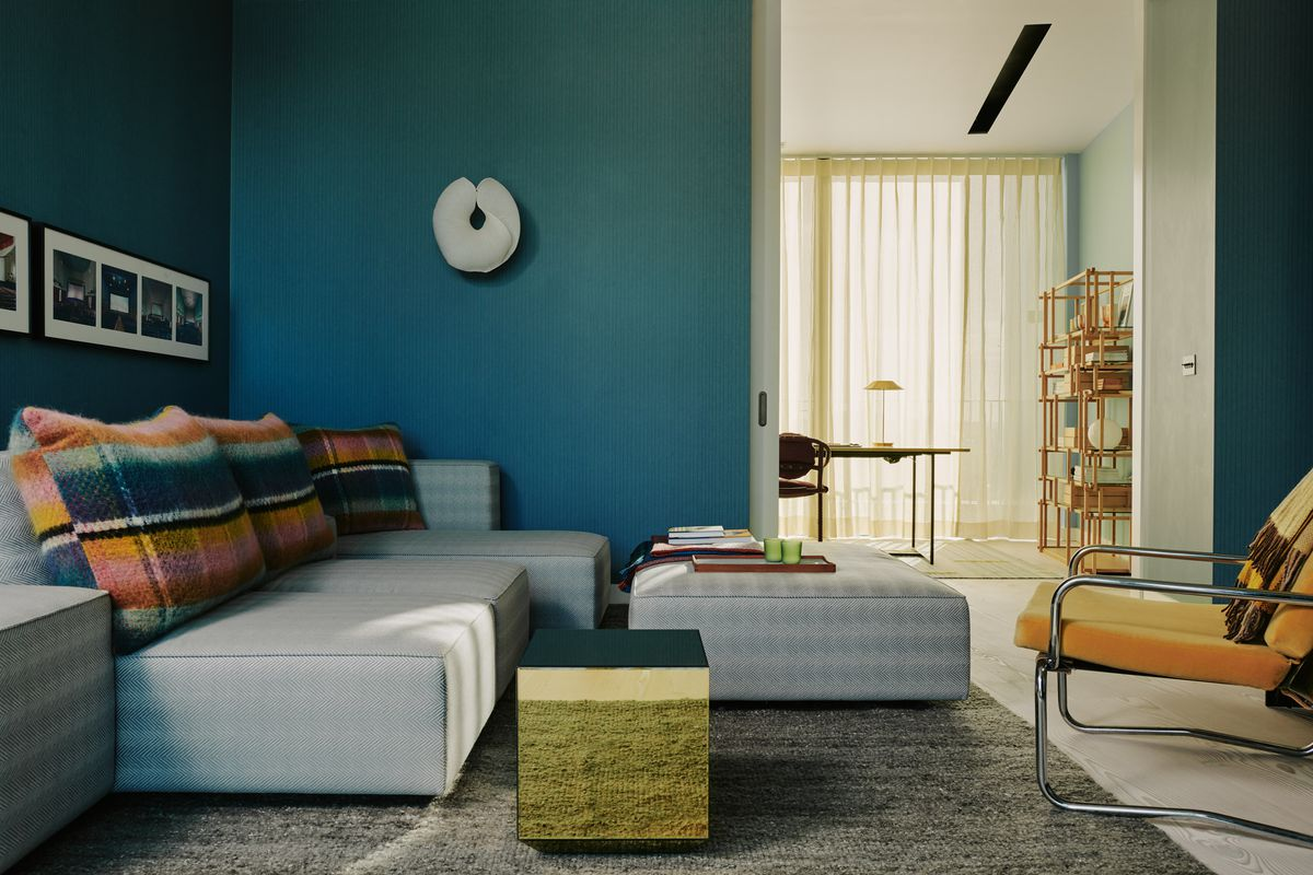 Living room with blue walls and plaid pillows.