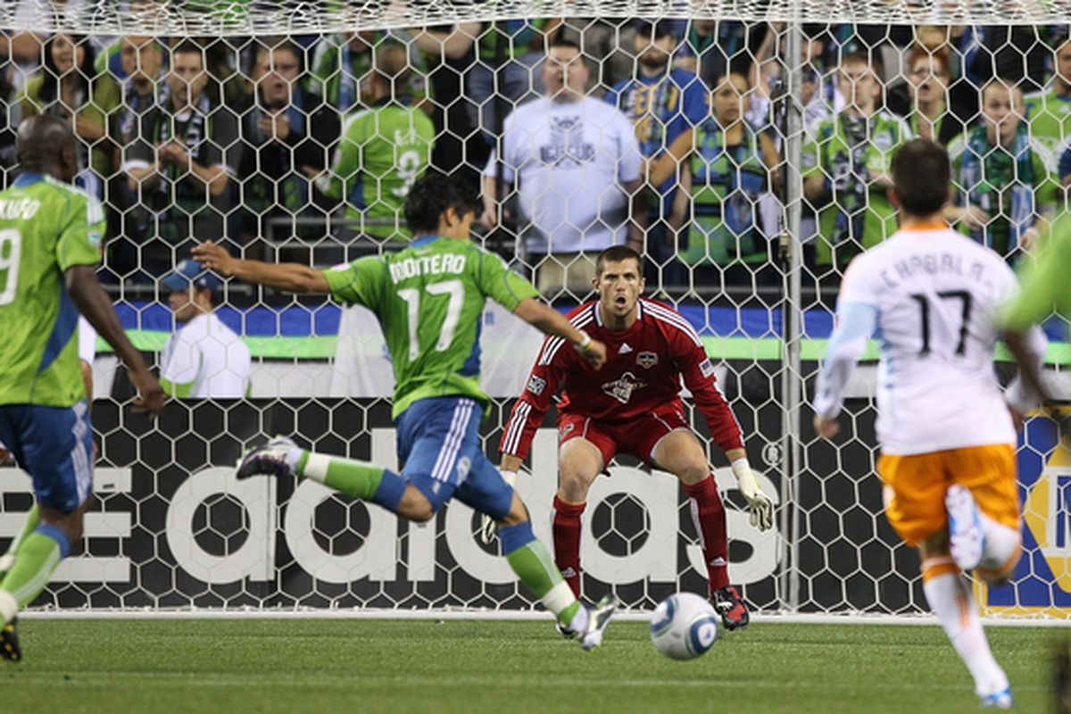 SEATTLE - AUGUST 08:  Fredy Montero #17 of the Seattle Sounders FC kicks a goal against goalkeeper Tally Hall #1 of the Houston Dynamo on August 8 2010 at Qwest Field in Seattle Washington. (Photo by Otto Greule Jr/Getty Images)
