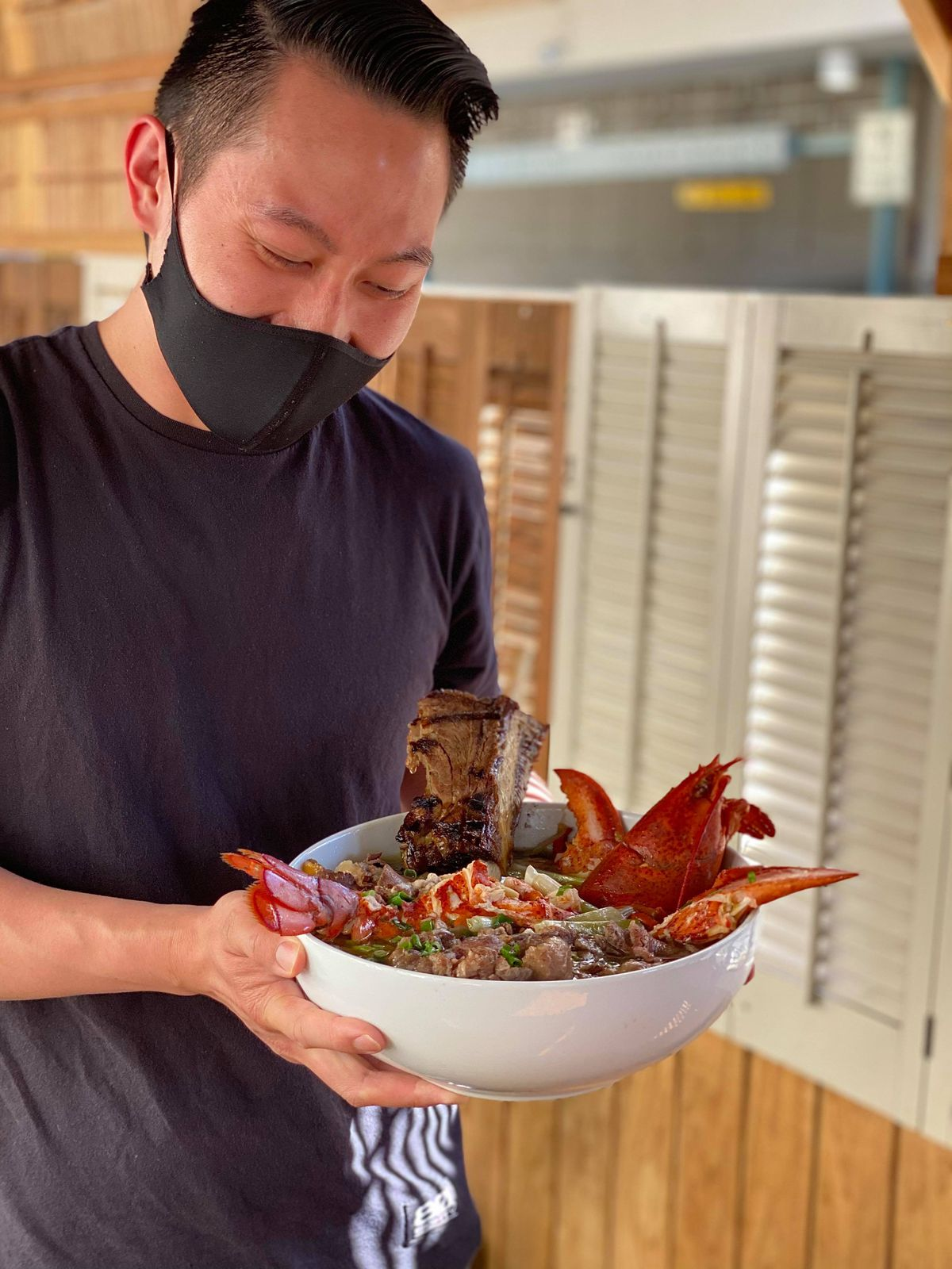 Gao Viet Kitchen owner and chef Viet Nguyen with a bowl of pho topped with a whole Maine lobster