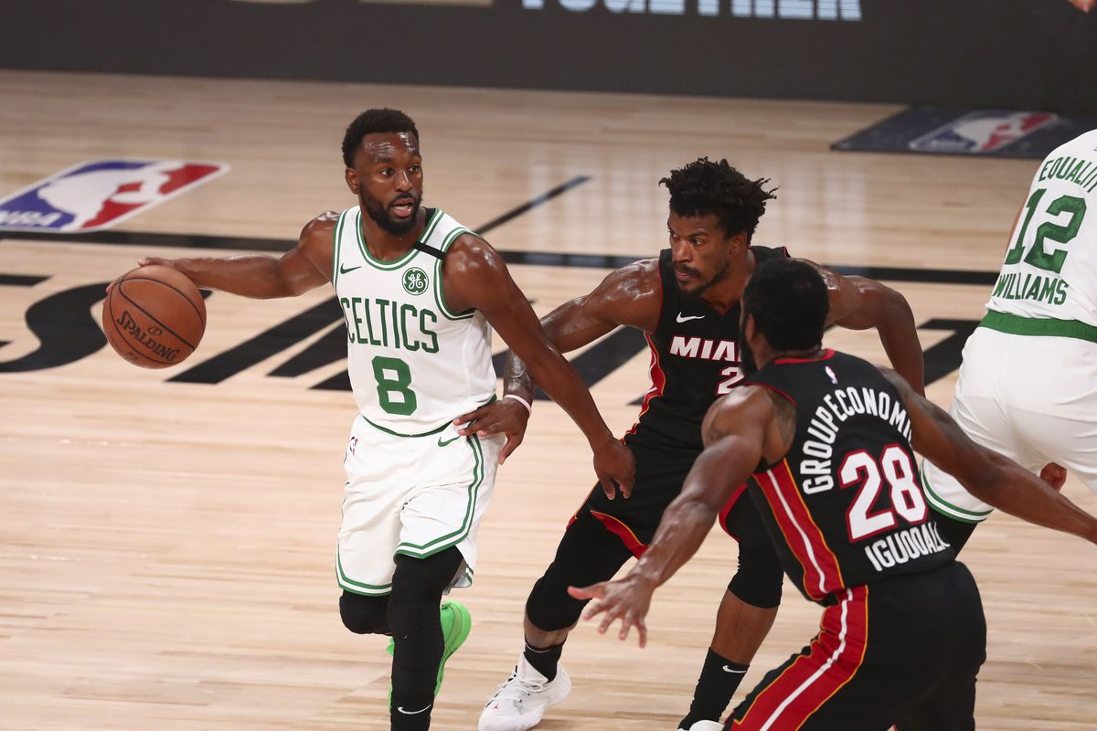 Boston Celtics guard Kemba Walker (8) controls the ball defended by Miami Heat forward Jimmy Butler (22) and guard Andre Iguodala (28) during second half in game six of the Eastern Conference Finals of the 2020 NBA Playoffs at AdventHealth Arena.