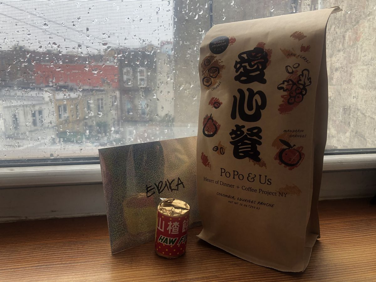 A decorated bag of coffee beans, an envelope, and a wrapped cylinder of candy set on a wooden windowsill