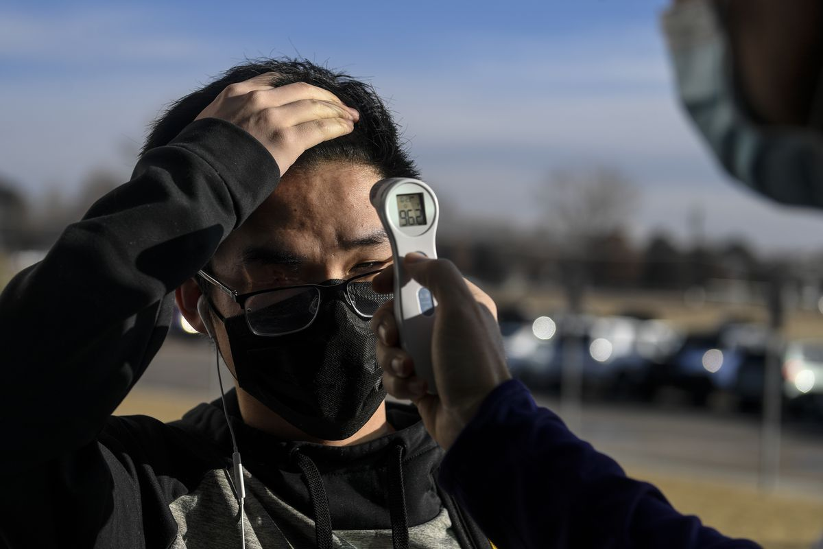 A teenage boy gets his temperature checked with a forehead thermometer outside a school.