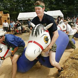 Matt Pelo, center, of Midway, and the Utah National Parks Council work to win the Buckaroo Bob inflatable horse race at the National Scout Jamboree at Fort AP Hill in Virginia Tuesday.