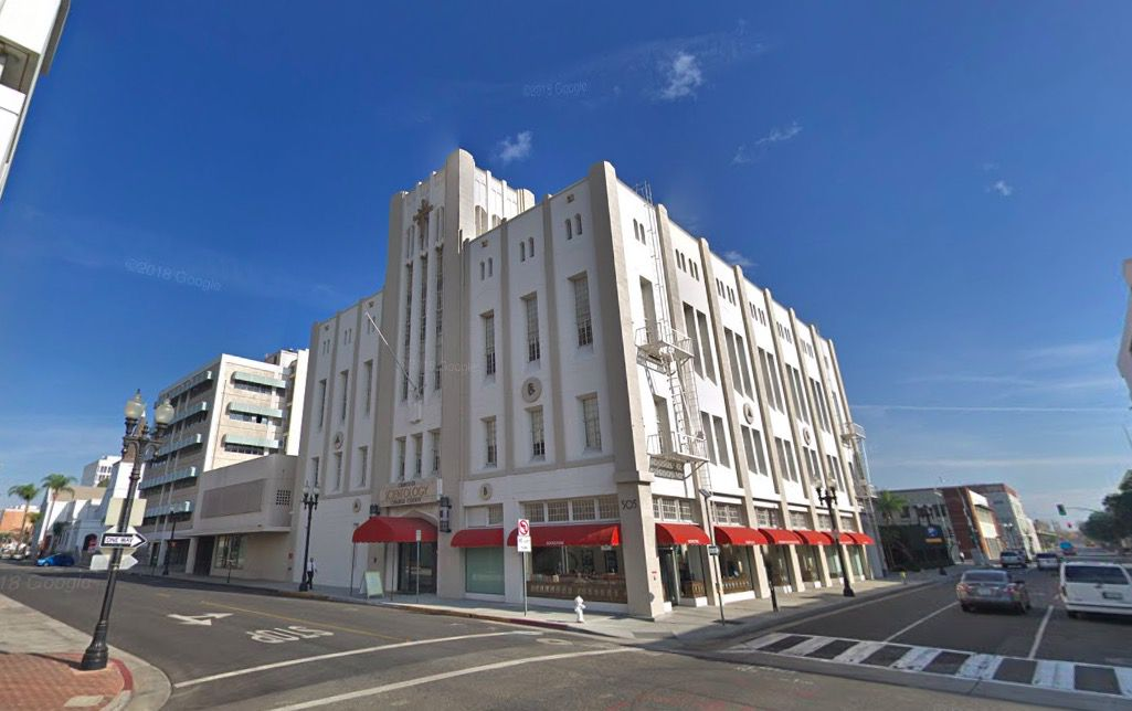 The exterior of the Scientology building in Santa Ana. The facade is white and there are red awnings over the windows on the ground level.