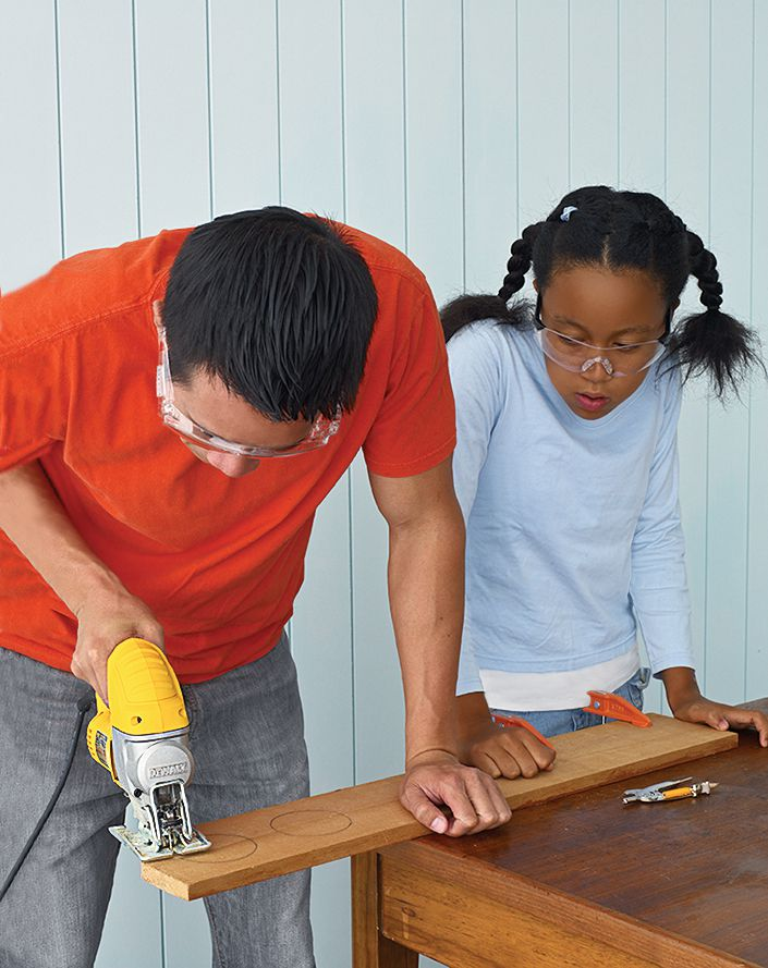 Person cutting wood cedar wood to make a bird feeder.