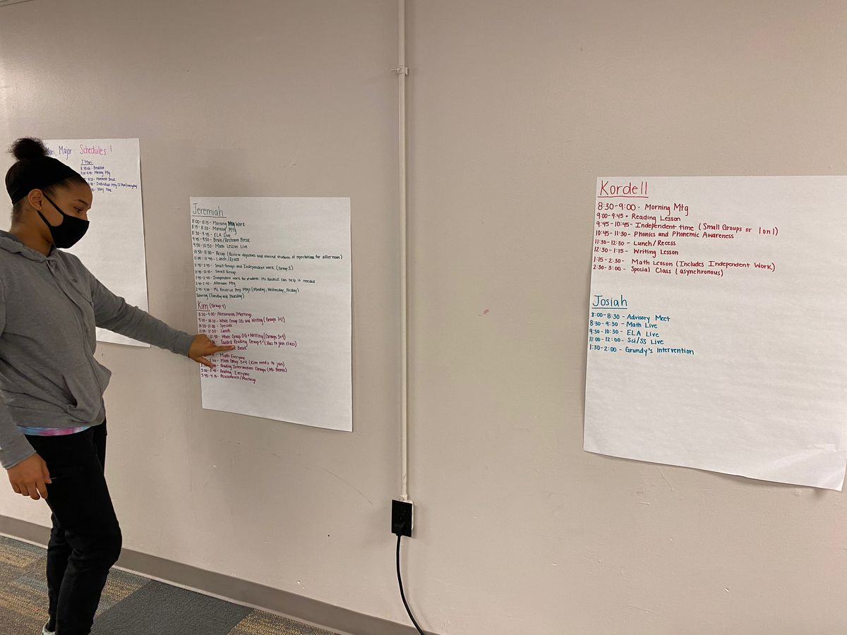 A young woman points to the three posters with students' names and class schedules for her learning pod group at the Christamore House on the westside of Indianapolis on Dec. 10, 2020. She is a e-learning specialist.