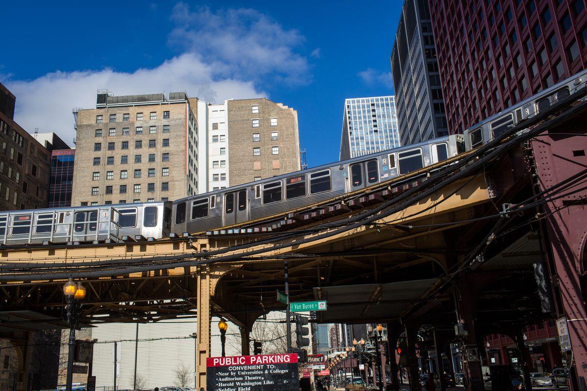 An el train passes on elevated tracks between buildings.