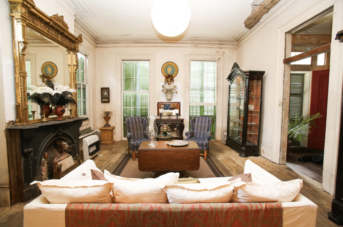 A romantically weathered living room with antiques and a large fireplace topped with a gilded mirror