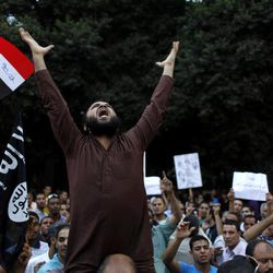 """FILE - In this Wednesday, Sept. 12, 2012 file photo, Egyptian protesters carry their national flag and a flag with Arabic that reads """"No God but Allah, and Mohammed is his prophet,"""" and chant anti U.S. slogans during a demonstration in front of the U.S. embassy in Cairo, Egypt, as part of widespread anger across the Muslim world about a film ridiculing Islam's Prophet Muhammad."""