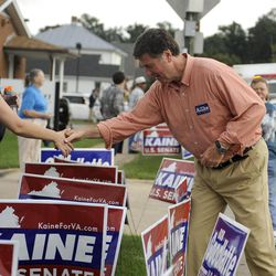 Republican senatorial candidate George Allen shakes the hand of a woman over a line of political signs supporting Democrat opponent Tim Kaine. Green space near roads and public areas were choked with political advertising during the Labor Day parade in Buena Vista, Va. The parade is the first big political event of the season in the Shenandoah Valley.
