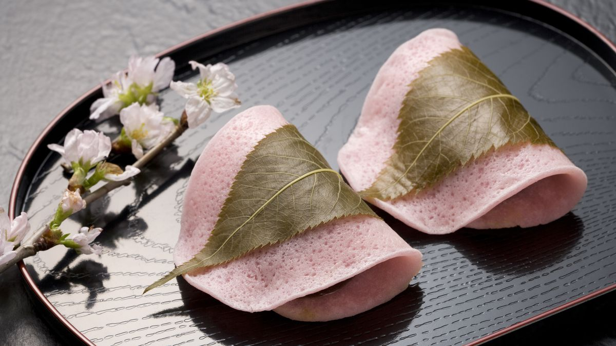 Two Sakura mochi — pink-hued rice cakes filled with red bean paste and wrapped in pickled cherry blossom leaves — on a black plate.