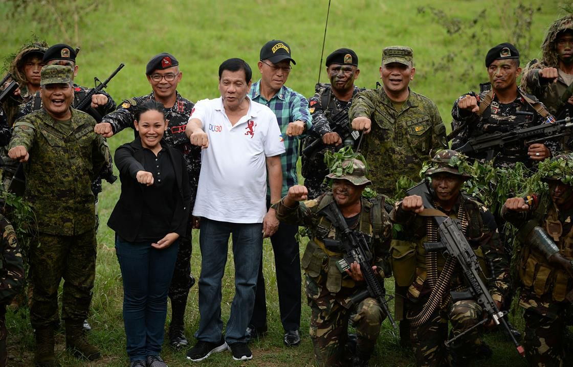 Duterte surrounded by soldiers with guns