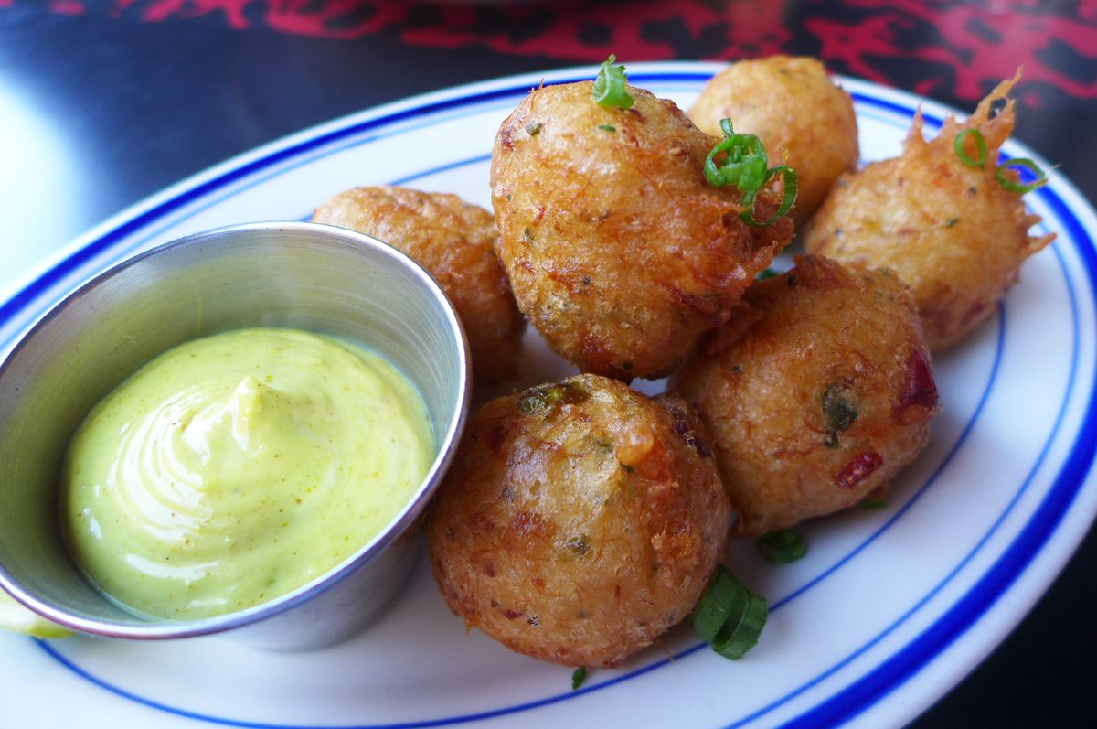 Round brown fritters with green dipping sauce on the side.