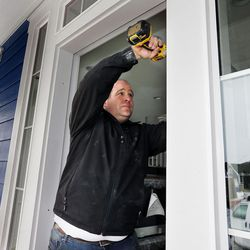 Blair Hill of Brighton Homes adjusts the front door of a new home in Farmington on Thursday, Feb. 4, 2016.