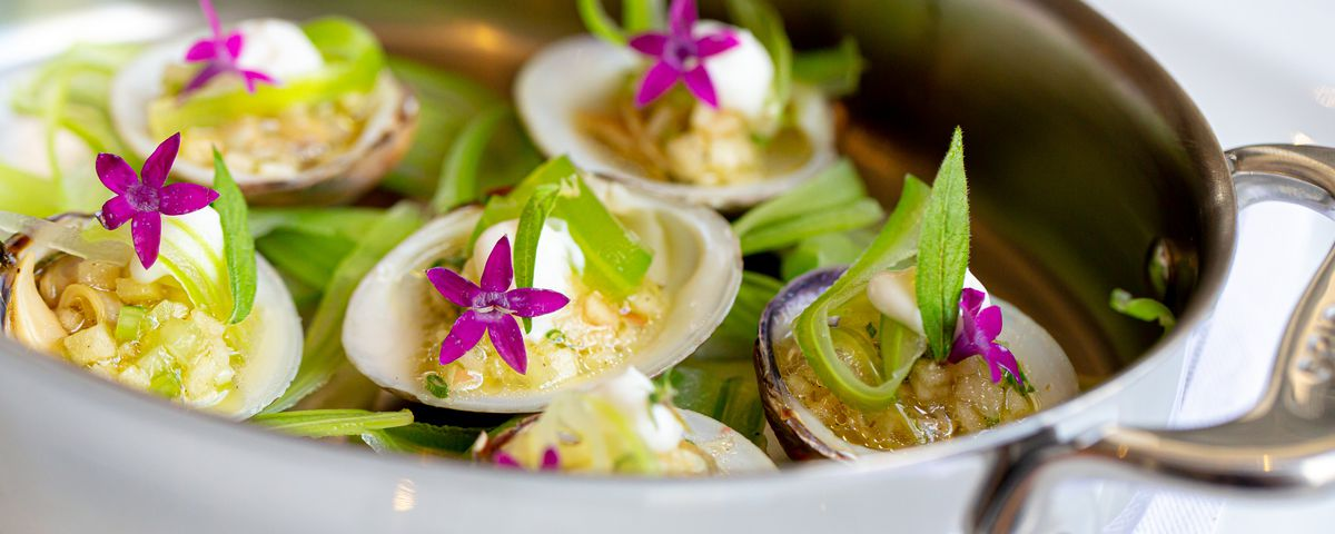 A metal dish with six clams on the half shell garnished with purple flowers and herbs
