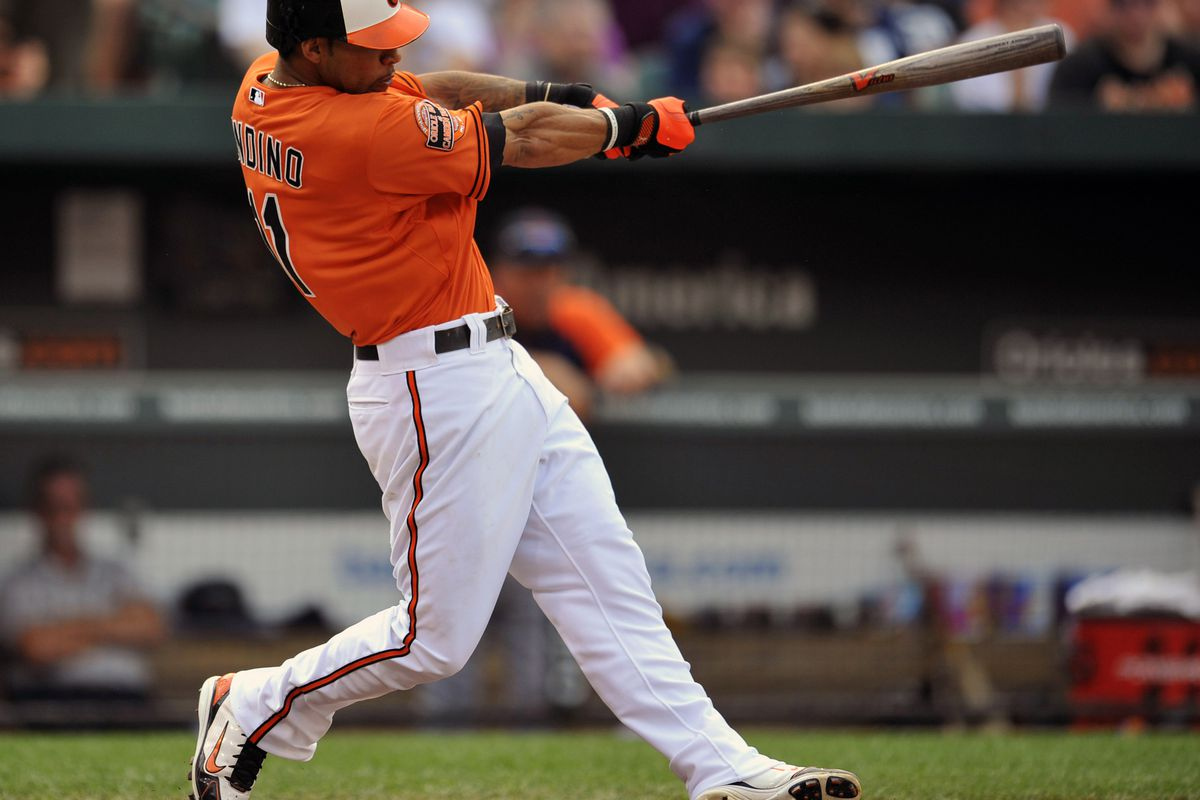 July 14, 2012; Baltimore, MD, USA; Baltimore Orioles second baseman Robert Andino (11) hits a two-run home run in the second inning against the Detroit Tigers at Oriole Park at Camden Yards. Mandatory Credit: Joy R. Absalon-US PRESSWIRE