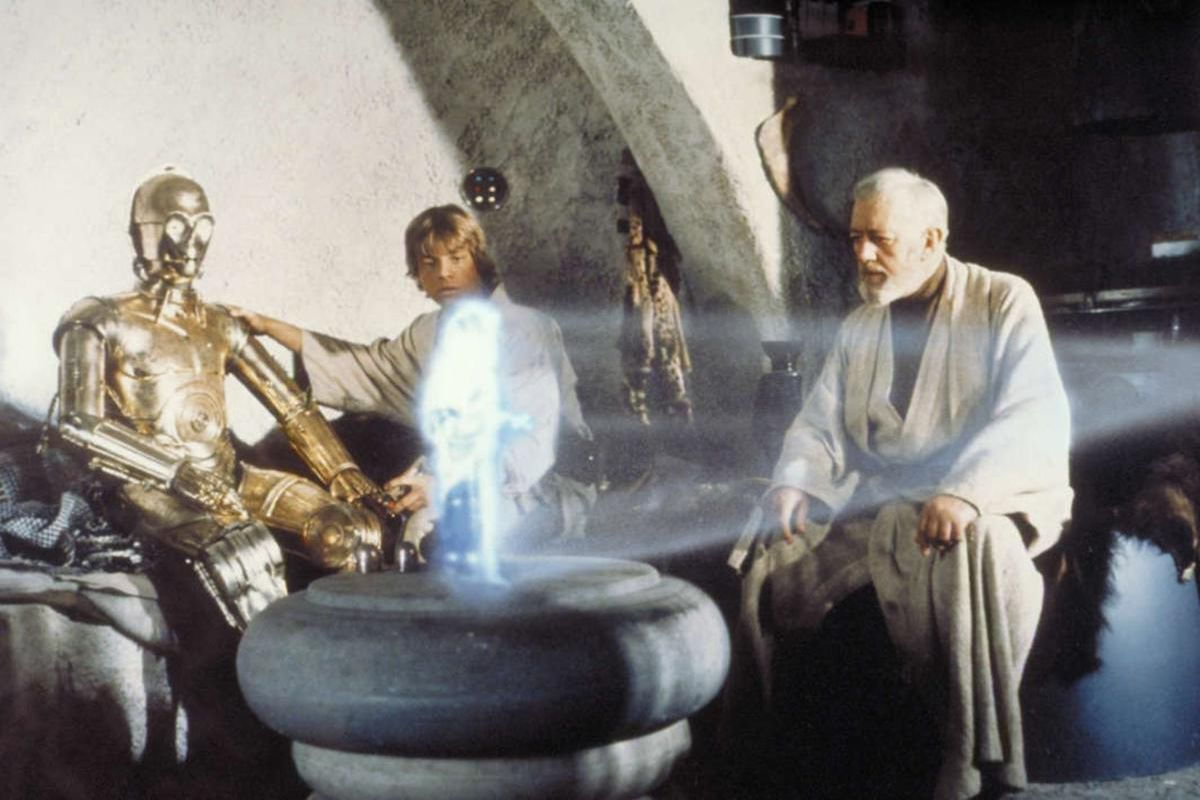 """Left, Anthony Daniels portraying C-3PO, Mark Hamill portraying Luke Skywalker and Alec Guinness portraying Ben Obi-Wan Kenobi look at a hologram of Princess Leia, portrayed by Carrie Fisher, in a scene from the original 1977 """"Star Wars"""" film."""