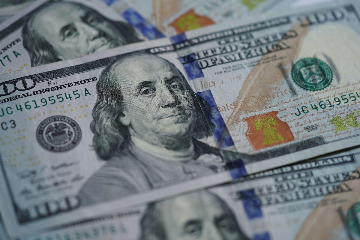 Hundred dollar bills lay on a table, depicting President Benjamin Franklin